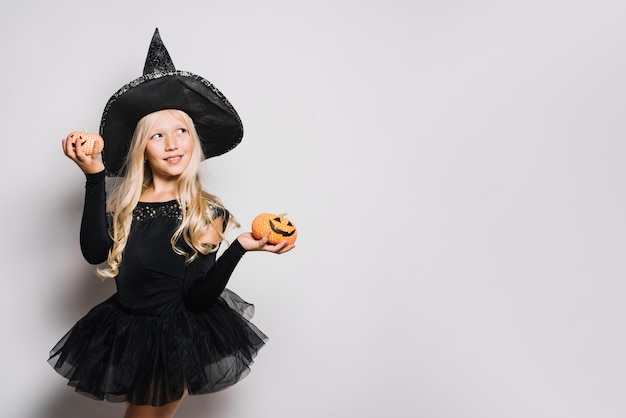 Dreamy little witch with jack-o-lanterns Free Photo