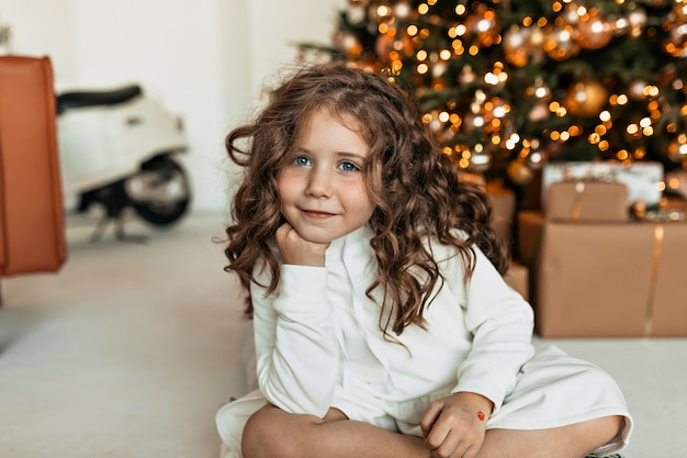 Мечтательная милая маленькая девочка с кудрями в белом вязаном свитере сидит перед елкой и ждет санта-клауса Бесплатные Фотографии