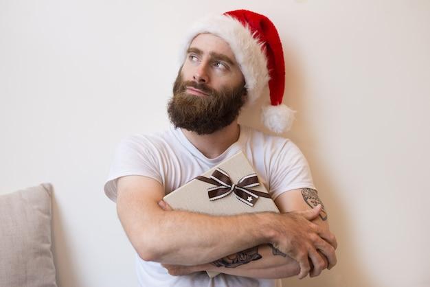 Dreamy man wearing santa hat and embracing gift box Free Photo