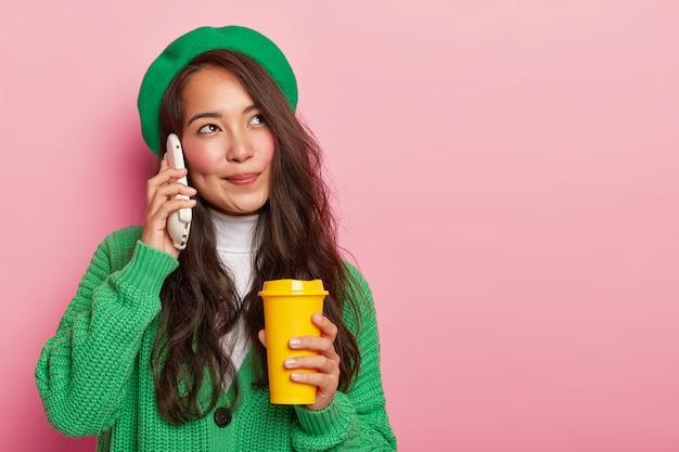 La ragazza asiatica dall'aspetto piacevole e sognante tiene lo smartphone vicino all'orecchio, gode di una piacevole conversazione mentre beve il caffè, ha lunghi capelli scuri, vestita con abiti eleganti verdi Foto Gratuite