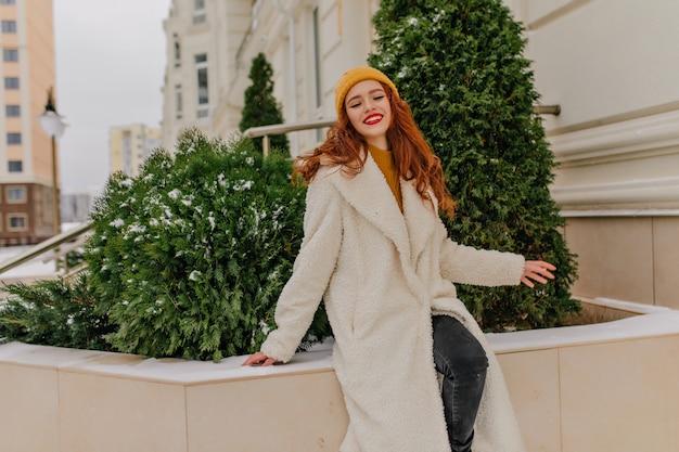Donna dai capelli rossi sognante in posa sulla strada in una giornata invernale. foto all'aperto di allegra ragazza caucasica che esprime emozioni positive. Foto Gratuite