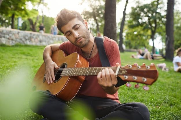 Uomo rilassato sognante, suonare la chitarra, sedersi sull'erba nel parco con lo strumento Foto Gratuite