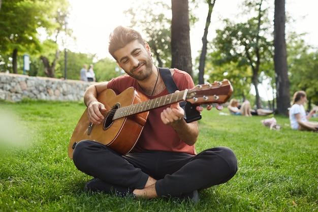 Мечтательный расслабленный мужчина играет на гитаре, сидит на траве в парке с инструментом Бесплатные Фотографии