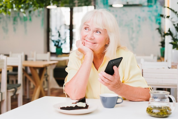 Dreamy smiling elderly woman with smartphone Free Photo