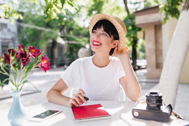 Мечтательная улыбающаяся девушка с короткой прической в соломенной летней шляпе пишет стихи во время обеда в саду Бесплатные Фотографии