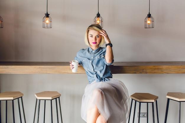 ブロンドの髪とピンクの唇が木の椅子とテーブルのあるコーヒーショップに座っている夢のようなスタイリッシュな女の子。彼女はコーヒーを一杯持って、彼女の髪に触れます 無料写真