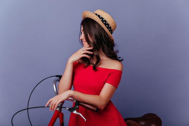 보라색 벽에 매력적인 미소로 포즈를 취하는 우아한 밀짚 모자에 꿈꾸는 여자. 자전거에 앉아 잠겨있는 갈색 머리 여성 모델. 무료 사진