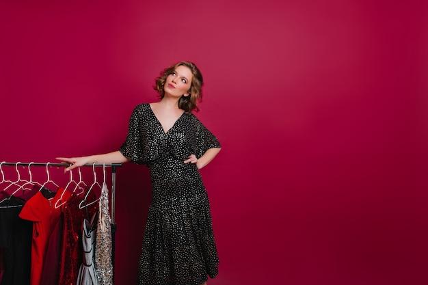 Мечтательная женщина в ретро черном платье смотрит вверх, позируя рядом с вешалками с одеждой Бесплатные Фотографии