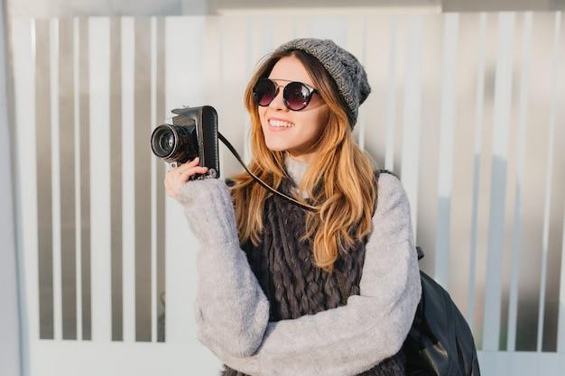 魅力的な笑顔で見上げる手にカメラとサングラスで夢のような女性。帽子と柔らかいニットのセーターを着ているインスピレーションを得た女性写真家の屋外のポートレート。 無料写真