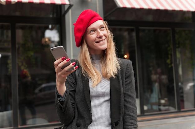 Мечтательная молодая привлекательная блондинка в модной одежде, хитро улыбаясь, глядя вверх, держа смартфон в поднятой руке Бесплатные Фотографии