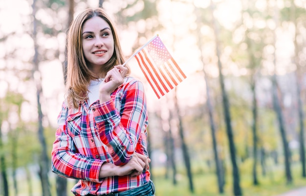 Dreamy young woman with small american flag Free Photo