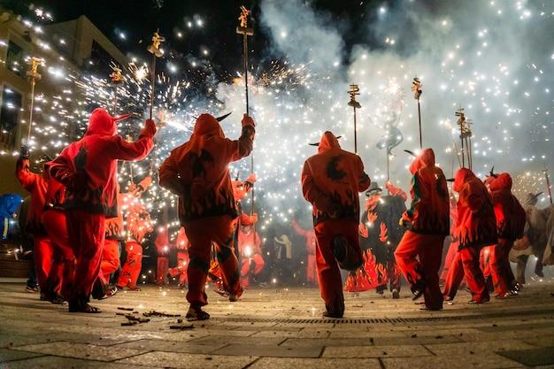 花火でパフォーマンスをする悪魔にdressした人々 Premium写真