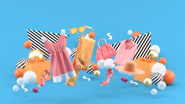 Dresses, pants, sweatshirts, hats, purses, high heels and sunglasses among colorful balls on blue. 3d rendering. Premium Photo