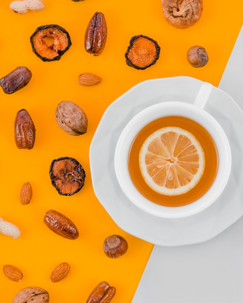 Dried apricot; dates; almonds; walnut; peanut and hazelnut with lemon tea cup on yellow and white backdrop Free Photo
