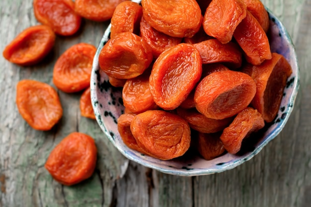 Dried apricots in a bamboo bowl on an old wooden. healthy dried fruit Premium Photo