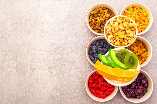Dried and candied fruit and cashew nuts in ceramic bowls Premium Photo