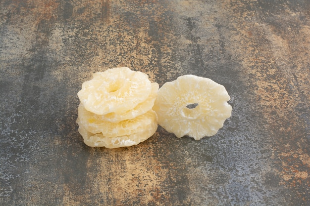 大理石の背景に乾燥した砂糖漬けのパイナップルリング。高品質の写真 無料写真