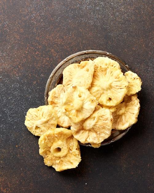 乾燥した砂糖漬けのパイナップルリング。茶色のコンクリート背景に甘い果物をスライスしました。上面図。 Premium写真