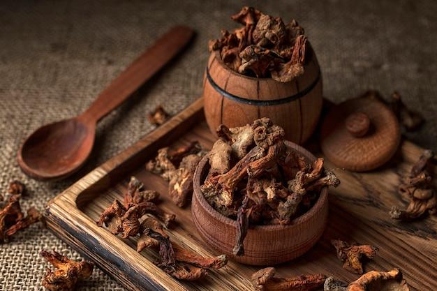Сушеные грибы лисички, на деревянной доске деревянной ложкой и деревянной бочкой Premium Фотографии