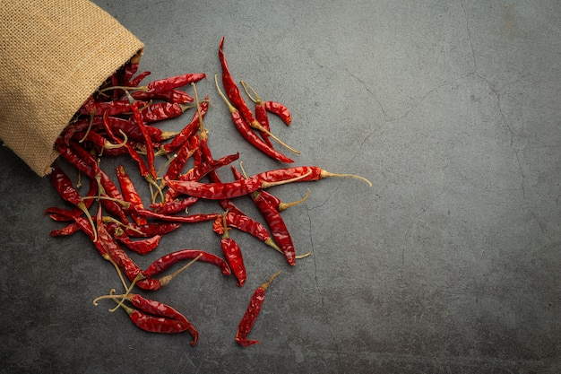 Dried chili pepper pouring out from sac to floor Free Photo
