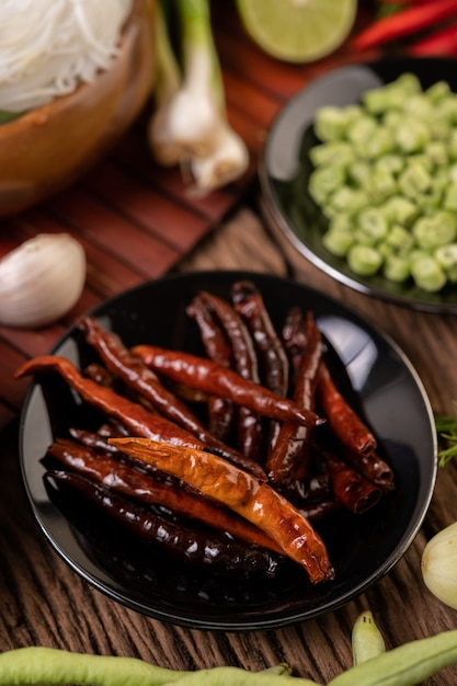 Сушеный перец чили, обжаренный на черной тарелке с чечевицей. на деревянный стол кладут огурцы и чеснок. Бесплатные Фотографии