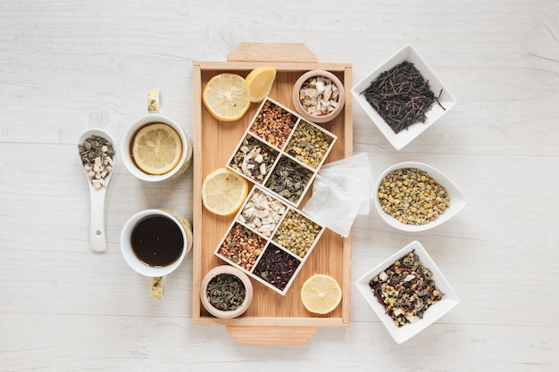 Dried chinese chrysanthemum flowers; herbs; tea and lemon slices on wooden tray Free Photo