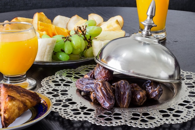 Dried date medjool palm fruits, fresh orange juice, samosa snack and fruit background concept iftar in the holy month ramadan Premium Photo