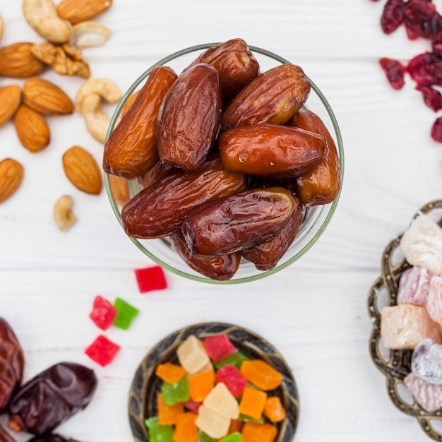 Dried dates fruit in bowl with different sweets Free Photo