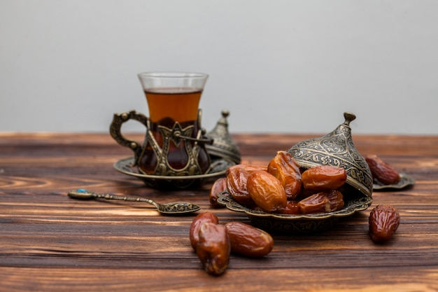 Dried dates fruit on plate with glass of tea Free Photo