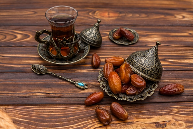 Dried dates fruit on small plate with glass of tea Free Photo