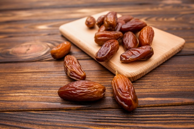 Dried dates fruit on wooden board on table Free Photo