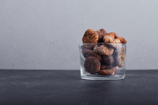 灰色の背景にガラスのカップで干しイチジク。 無料写真