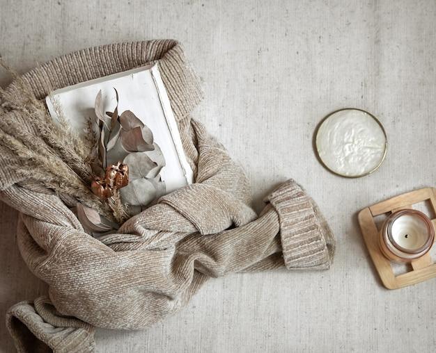 Букет сухих цветов на теплый пастельный свитер и вид сверху свечи, концепция осеннего уюта. Premium Фотографии