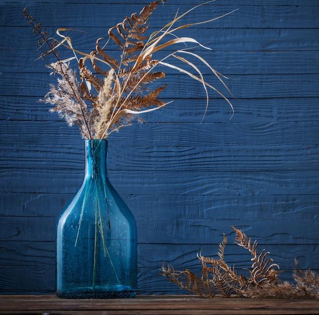 Сухие цветы в стеклянной вазе на деревянном столе на синем фоне Premium Фотографии