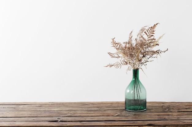 Сухие цветы в вазе на деревянном столе на белом фоне Premium Фотографии