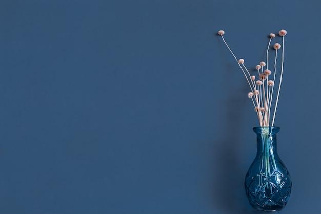 Fiori secchi e un vaso su una parete blu. Foto Gratuite