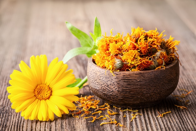 Dried and fresh marigold (calendula) flowers in a bowl on wooden rustic background. Premium Photo