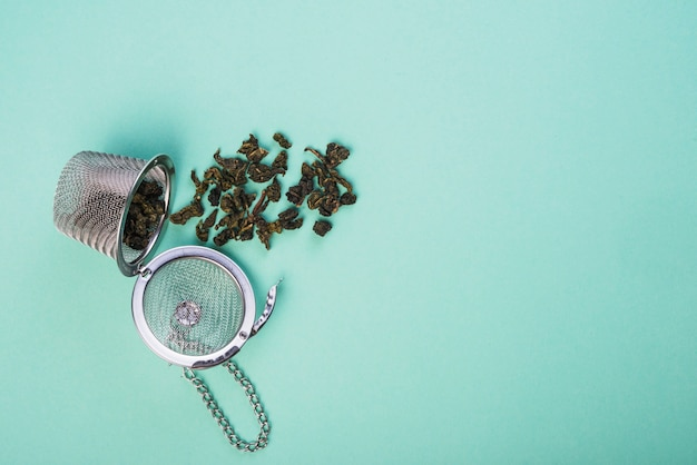 Dried herb tea spilled from the tea strainer on blue backdrop Free Photo