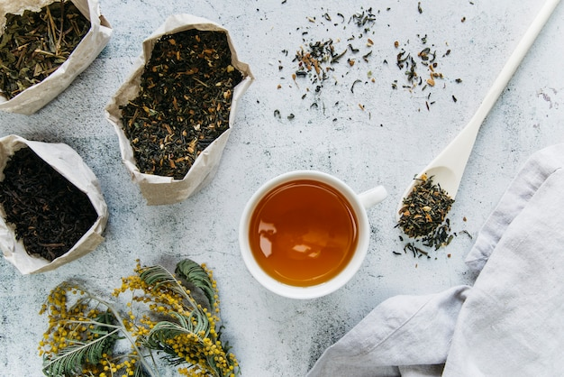 Dried herbal tea with tea cup on concrete backdrop Free Photo