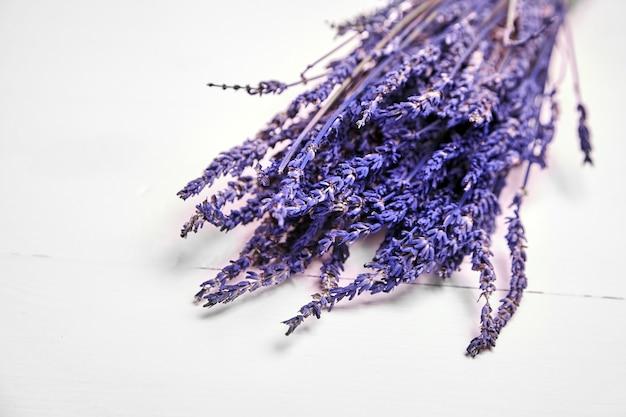 木製のテーブルの上の乾燥したラベンダーの花、白い背景の上の紫色のラベンダー植物の束 Premium写真