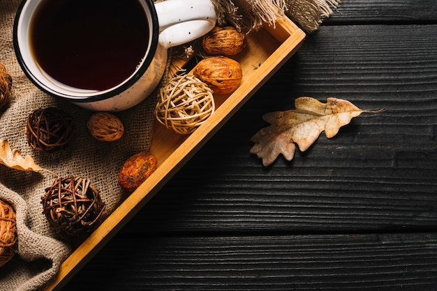 Dried leaf near tray with beverage and decorations Free Photo