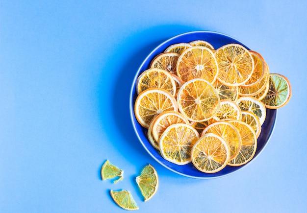 Dried orange fruit slices on a blue ceramic plate, blue paper fruit minimal concept. Premium Photo
