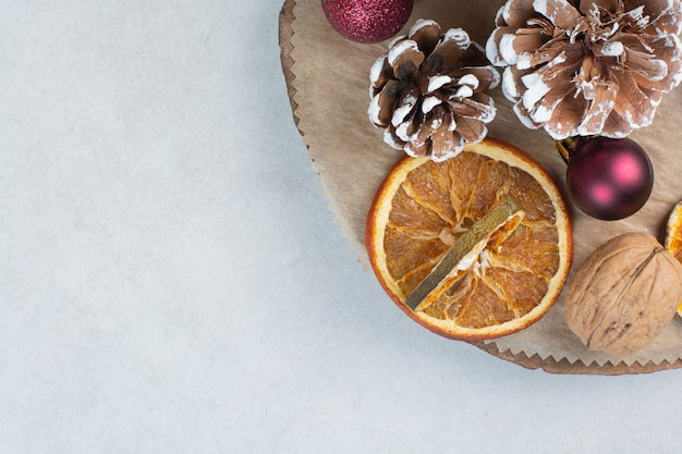 木の板に松ぼっくりとクリスマスボールが付いた乾燥オレンジ。高品質の写真 無料写真