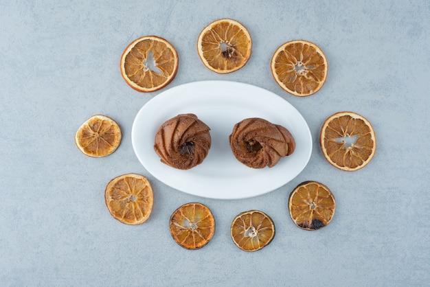 白い背景の上の2つのおいしいカップケーキと乾燥オレンジ 無料写真