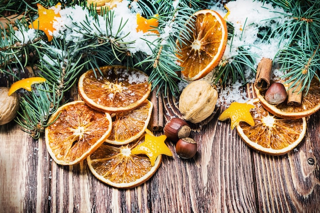 Dried oranges with nuts and fir branches Premium Photo