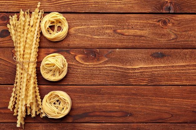 Dried pasta on wooden background Premium Photo