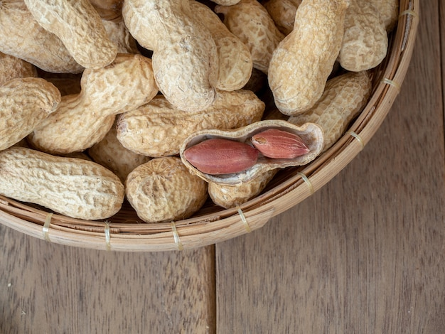 Dried peanuts in shells on peanuts background on wooden table Premium Photo