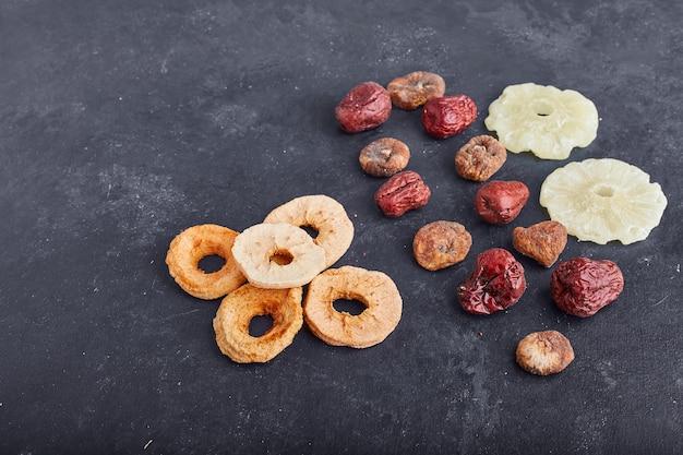 灰色の背景に乾燥パイナップル、リンゴのスライスとプラム。 無料写真