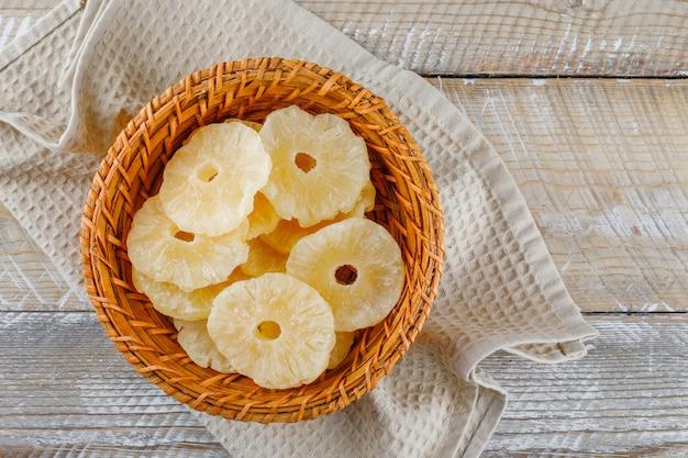 キッチンタオルの上のバスケットにパイナップルを乾燥 無料写真