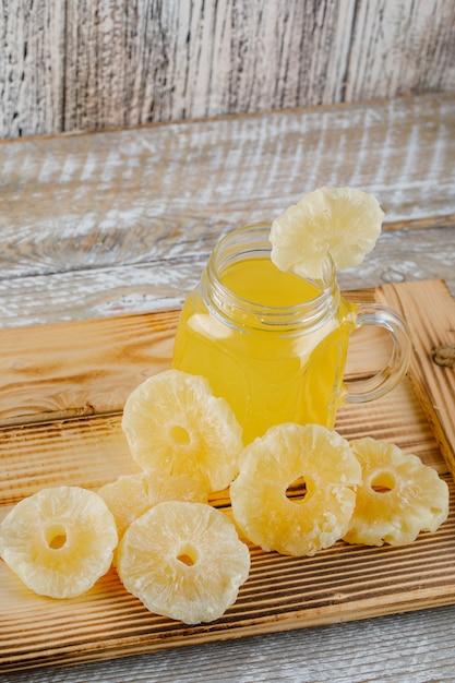 木製の表面にジュースとトレイに乾燥パイナップル 無料写真